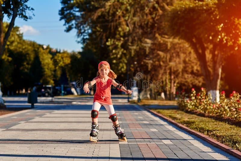 Flickaridning på rullskridskor i utomhus- skateparksommar Barn i en röd dräkt för rullarna arkivfoton