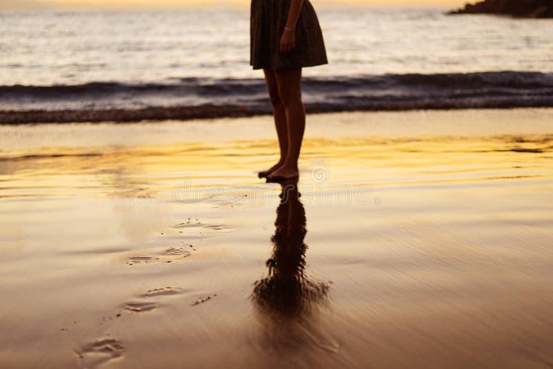 Flickas ben på solnedgången på stranden royaltyfri bild