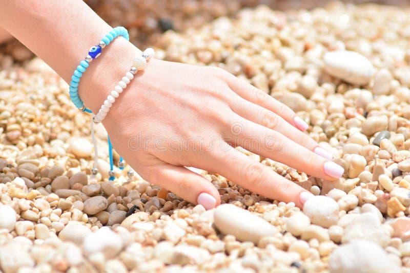 Flickas hand med ett modesommararmband i nautisk stil p? kiselstenar f?r ett hav royaltyfri fotografi