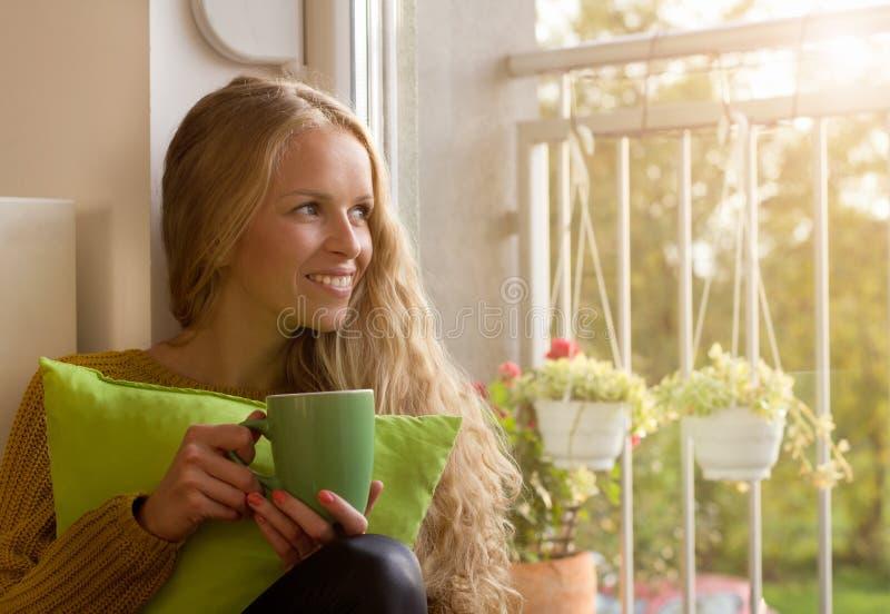 Flickasammanträde bredvid fönster med kopp te arkivbilder