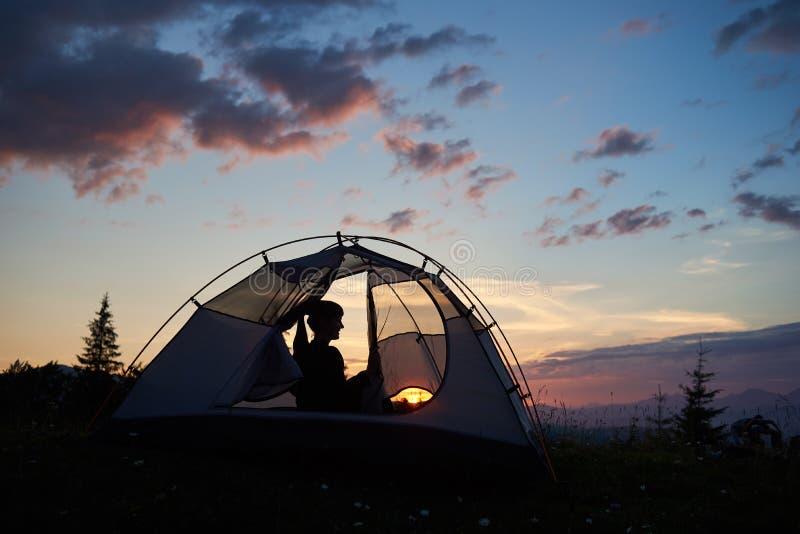 Flickasammanträde för bakre sikt i tält under den blåa himlen för afton som tycker om solnedgången royaltyfria foton