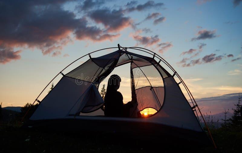 Flickasammanträde för bakre sikt i tält under den blåa himlen för morgon som tycker om gryningen royaltyfri bild