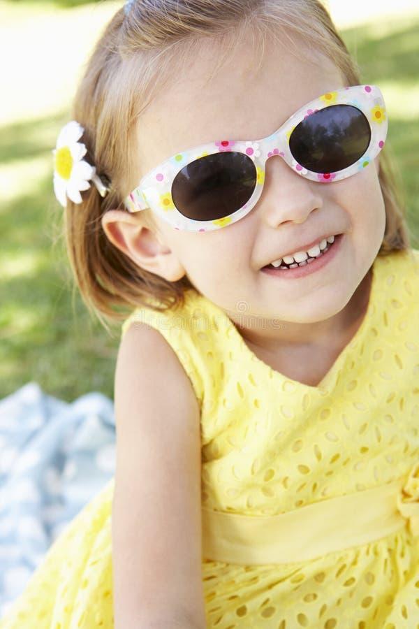 Flickasammanträde i bärande solglasögon för trädgård royaltyfria foton