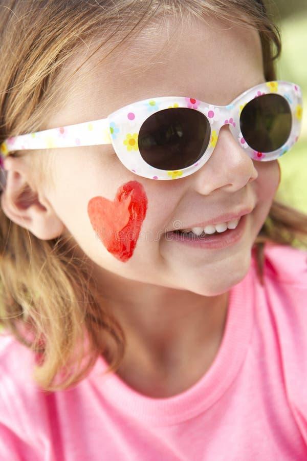 Flickasammanträde i bärande solglasögon för trädgård royaltyfri foto