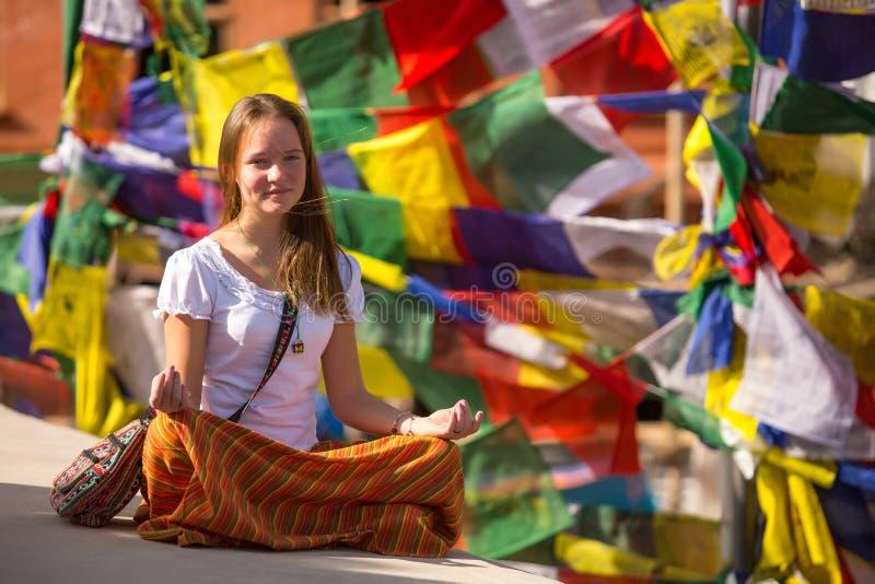 Flickasammanträde i den Lotus positionen på buddistisk stupa Resor royaltyfri bild