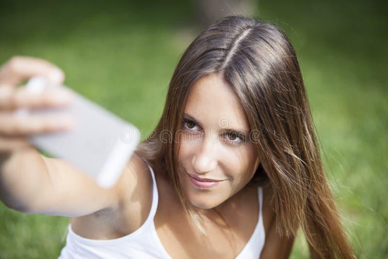 Flickasammanträde i parkera och gör selfie arkivbilder