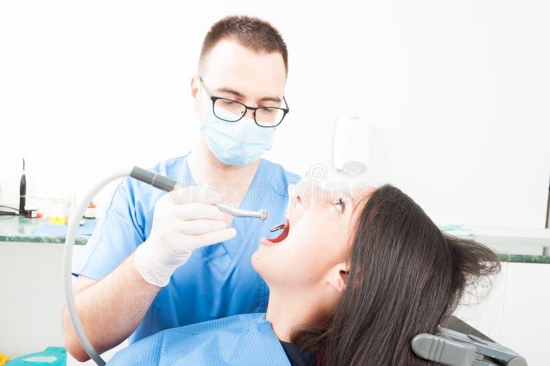 Flickasammanträde i tandläkarestol som har en professionell som borstar för arkivfoton