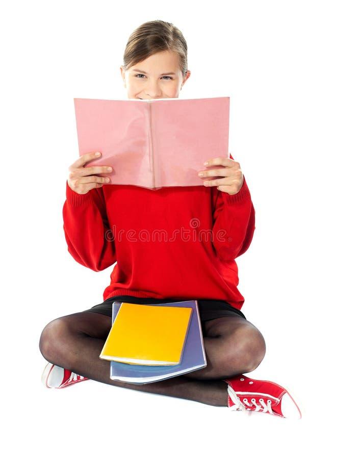 Flickasammanträde med böcker på henne varv royaltyfri foto
