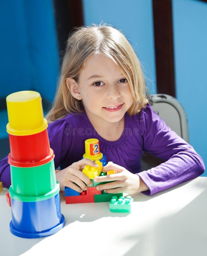 Flickasammanträde med leksaker på skrivbordet i förträning royaltyfria bilder