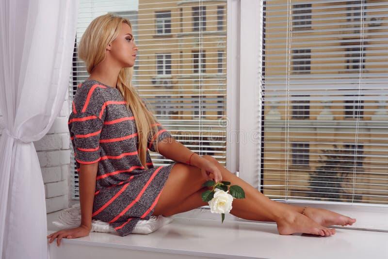 Flickasammanträde nära fönstret royaltyfria bilder