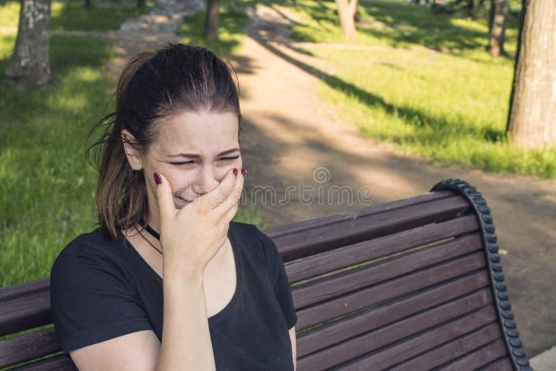 Flickasammanträde och gråt på en parkerabänk royaltyfria bilder