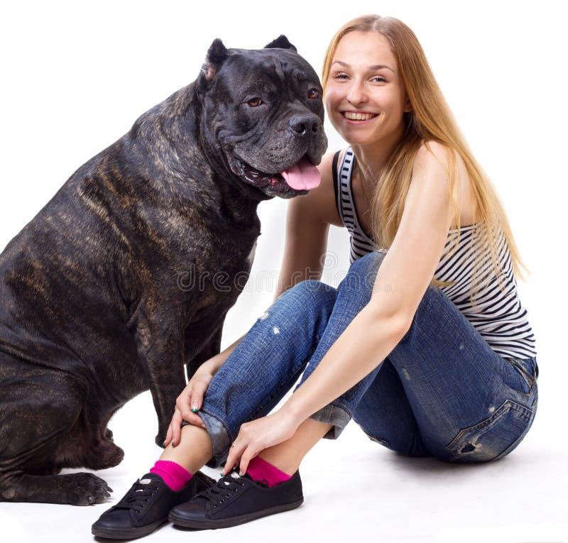 Flickasammanträde och leende bredvid hans hund Cane Corso Fyrkantig kantjustering royaltyfri bild