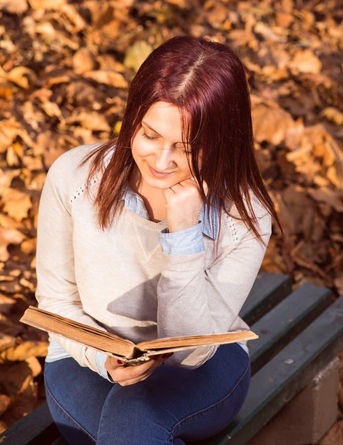 Flickasammanträde på bänk i tillflykt och läsning en bok royaltyfria bilder