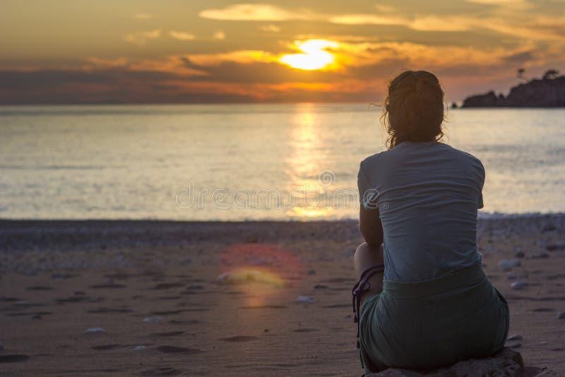 Flickasammanträde på den sandiga stranden nära medelhavet på solnedgången royaltyfri bild
