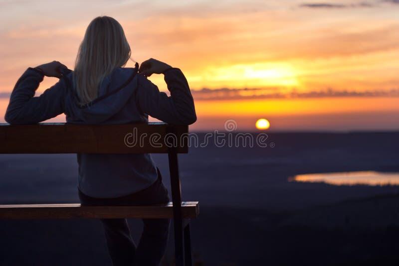Flickasammanträde på en banch på solnedgången arkivfoto
