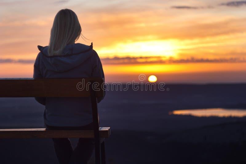 Flickasammanträde på en banch på solnedgången fotografering för bildbyråer