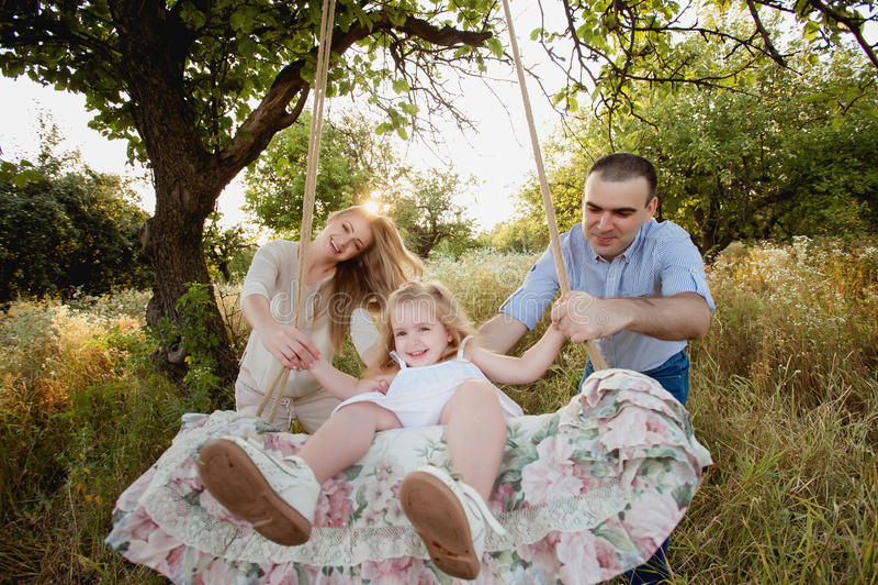 Flickasammanträde på en gunga, fader på modern som skjuter på naturen, lycklig familj, föräldrar, leende, glädje arkivfoto