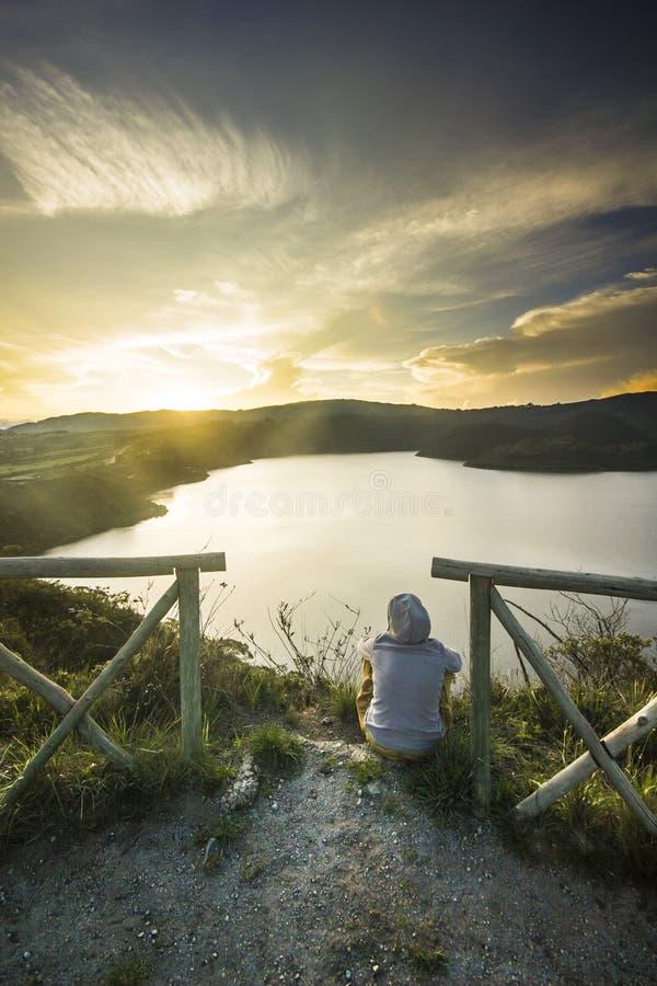 Flickasammanträde på en kant av krater med sjön inom royaltyfri fotografi