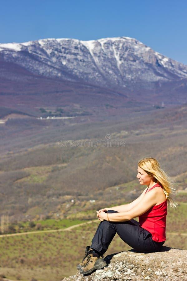 Flickasammanträde på en klippa i bergen fotografering för bildbyråer