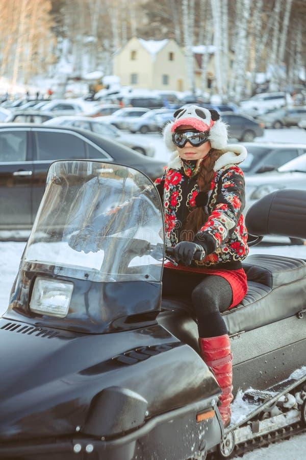 Flickasammanträde på en snövessla royaltyfria bilder