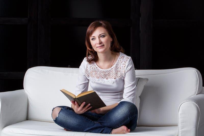 Flickasammanträde på en vit soffa royaltyfri foto