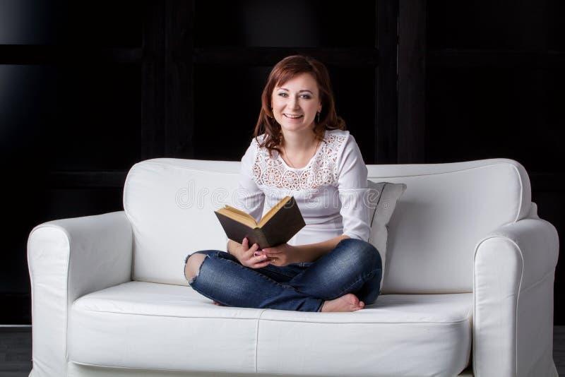 Flickasammanträde på en vit soffa arkivbilder