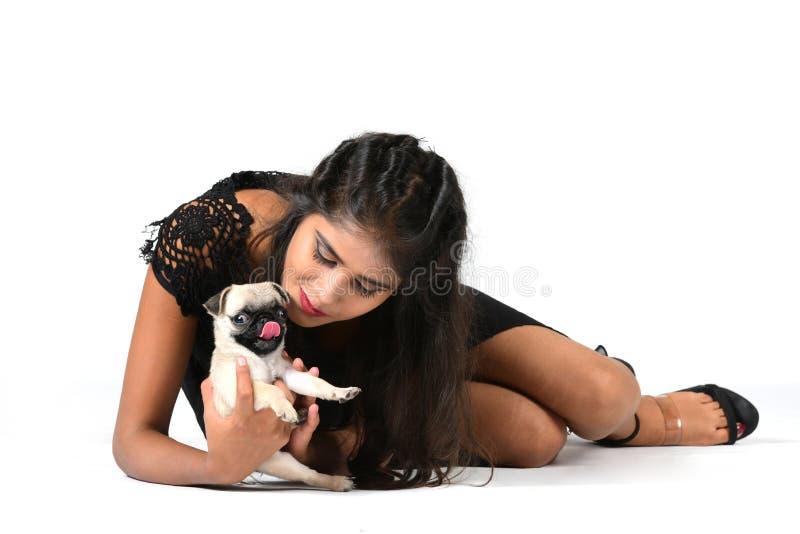Flickasammanträde på golvet som rymmer en gullig liten mopshund arkivfoto