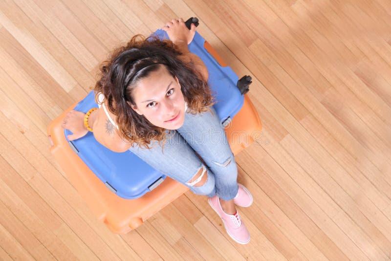 Flickasammanträde på resväskor royaltyfri foto
