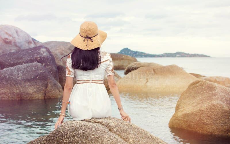 Flickasammanträde på sjösidan vaggar royaltyfria foton