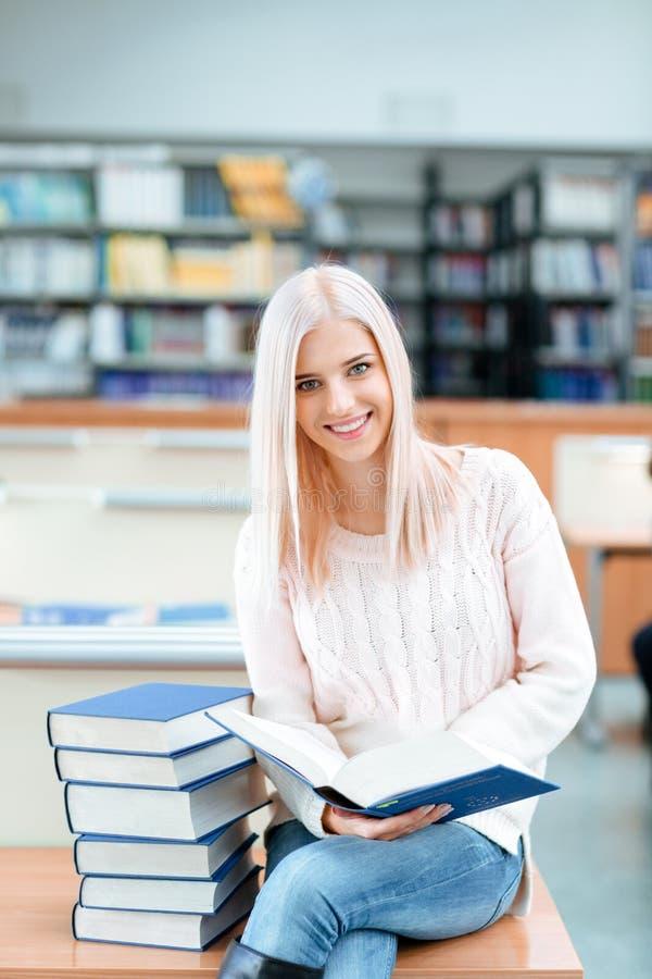 Flickasammanträde på skrivbordet med högen av böcker royaltyfri fotografi