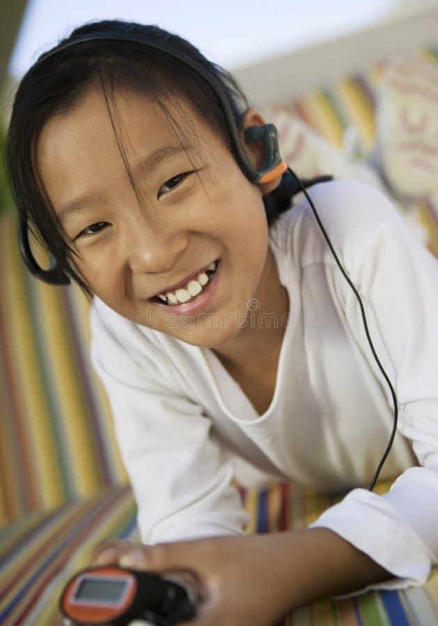 Flickasammanträde på soffan som lyssnar till ståenden för spelare MP3 royaltyfria foton