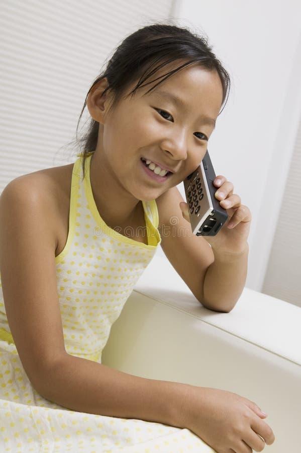 Flickasammanträde på soffan som talar på den sladdlösa telefonen royaltyfria bilder