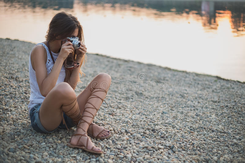 Flickasammanträde på stranden och fotografera royaltyfri bild