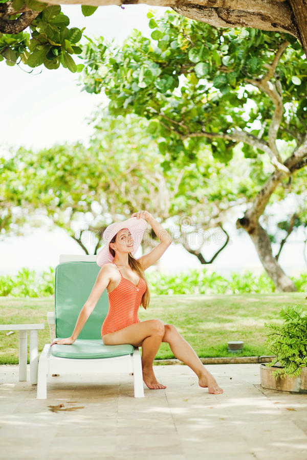 Flickasammanträde på sunbed nära trädet arkivbild