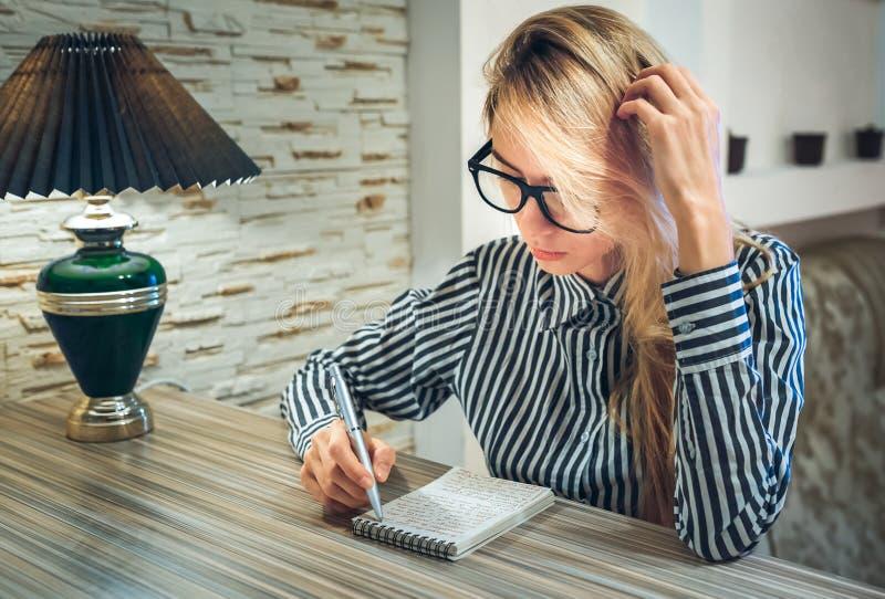 Flickasammanträde på tabellen och skriver i pappers- belopp för en anteckningsbok arkivfoton