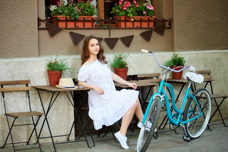 Flickasammanträde på terrass av gatakafét nära den retro cykeln royaltyfria foton