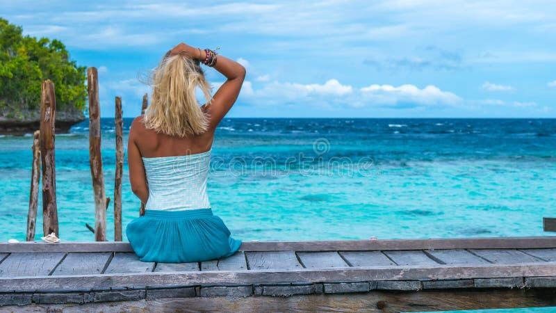 Flickasammanträde på träpir av en Homestay som ser in i det blåa havet, Gam Island, västra Papuan, Raja Ampat, Indonesien royaltyfria foton