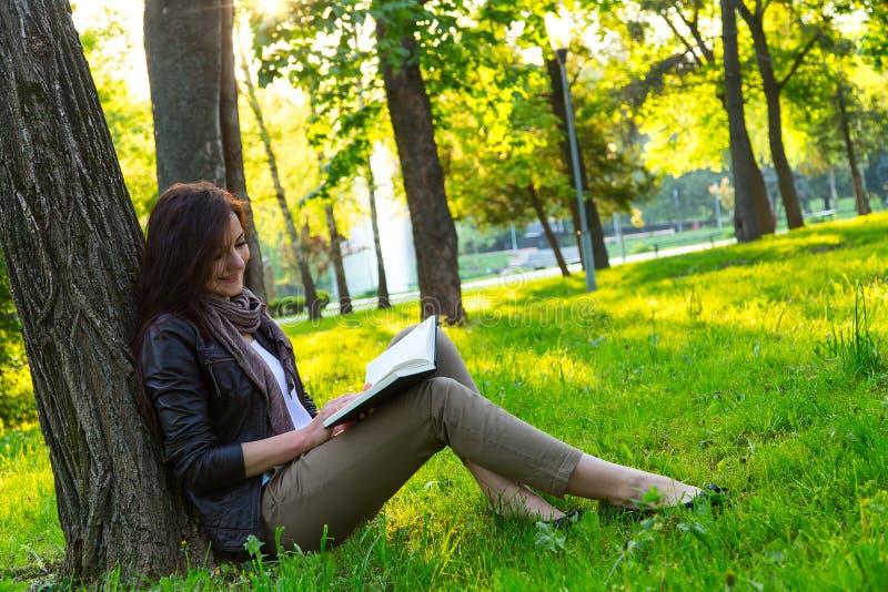 Flickasammanträde parkerar den lästa boken royaltyfri fotografi