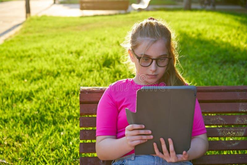 Flickasammanträde parkerar på bänken som spelar med minnestavlan arkivbild