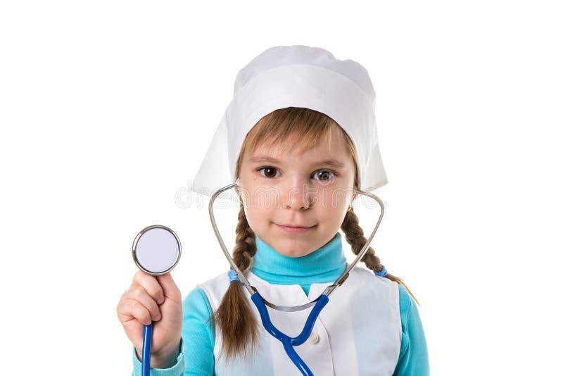 Flickasjuksköterska i den vita likformign med stetoskopet i öronen Rymma stetoskopet på förgrunden Landskap royaltyfri bild