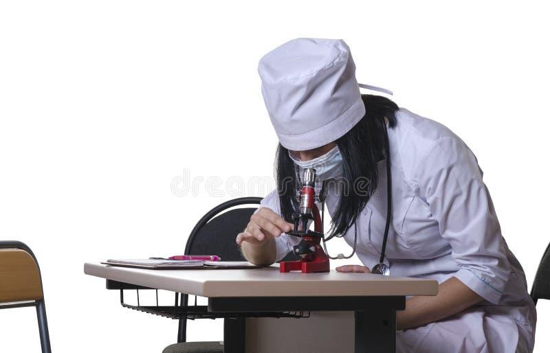 Flickasjuksköterskan undersöker blodanalys genom att använda ett mikroskop arkivbild