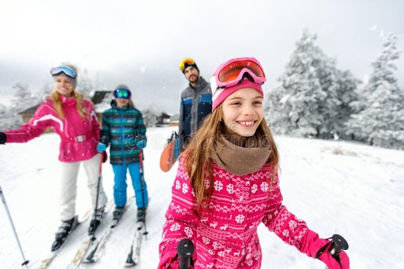 Flickaskidåkareskidåkning med familjen på berget royaltyfri fotografi