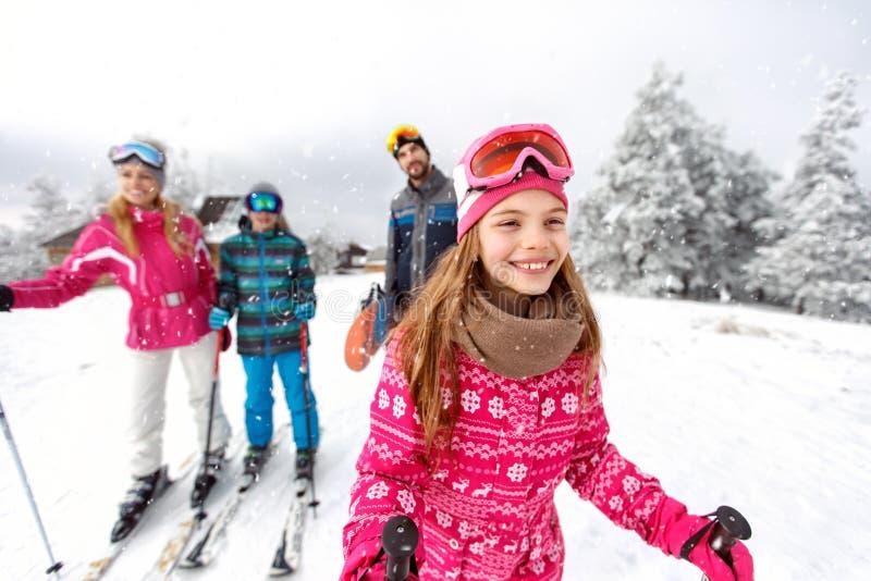 Flickaskidåkareskidåkning med familjen på berget royaltyfri bild