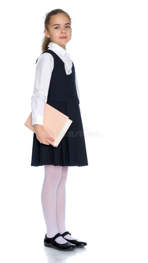 Flickaskolflicka med boken royaltyfri bild