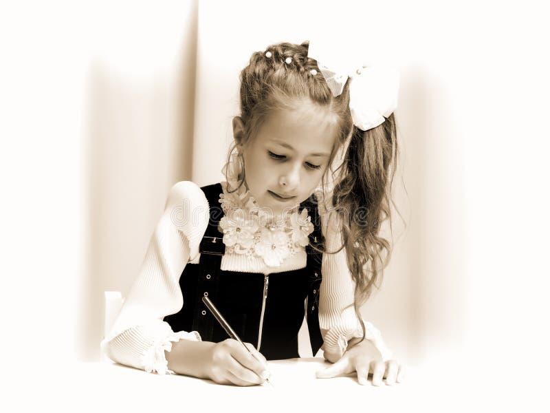 Flickaskolflickan skriver i anteckningsbok arkivfoton