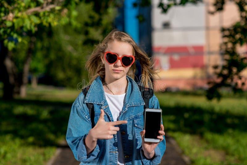 Flickaskolflickatonåring Sommar i natur Formad solglasögonhjärta I hans händer rymmer en smartphone begreppet av nytt arkivbilder