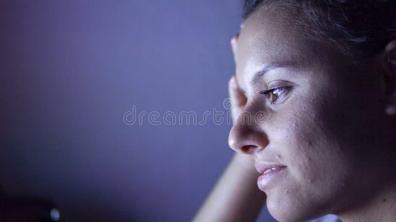 Flickaskratt, som hon håller ögonen på en rolig video på en minnestavla arkivfoto