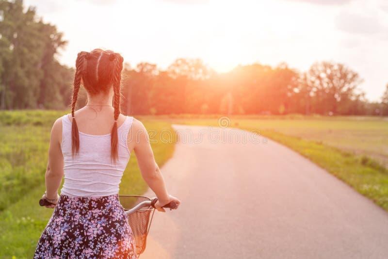 Flickaslutet med cykeln p? sommarsolnedg?ngen p? v?gen i staden parkerar upp Cykla ner gatan som arbetar p? sommarsolnedg?ngen royaltyfria bilder