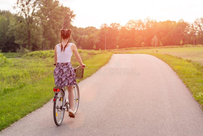 Flickaslutet med cykeln p? sommarsolnedg?ngen p? v?gen i staden parkerar upp Cykla ner gatan som arbetar p? sommarsolnedg?ngen arkivfoto