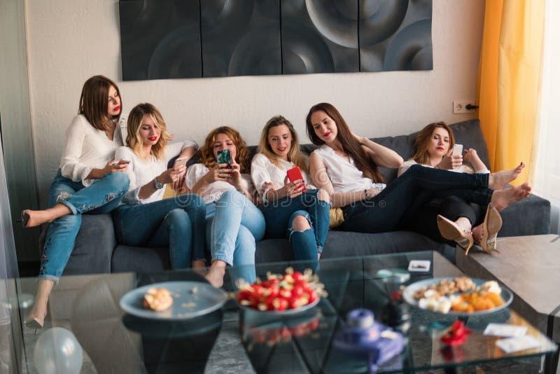 Flickasmartphoneparti, alla flickor som håller ögonen på smartphones arkivbilder